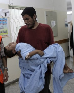 A man carries a Palestinian child to be treated for wounds on 10 September at the Al-Najjar hospital in Rafah, southern Gaza Strip AFP PHOTO/ SAID KHATIB