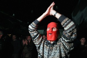 A Russian opposition supporter, wearing a red balaclava, shouts and applauses during a concert in support of Pussy Riot and other political prisoners in a club in Saint-Petersburg AFP PHOTO / OLGA MALTSEVA