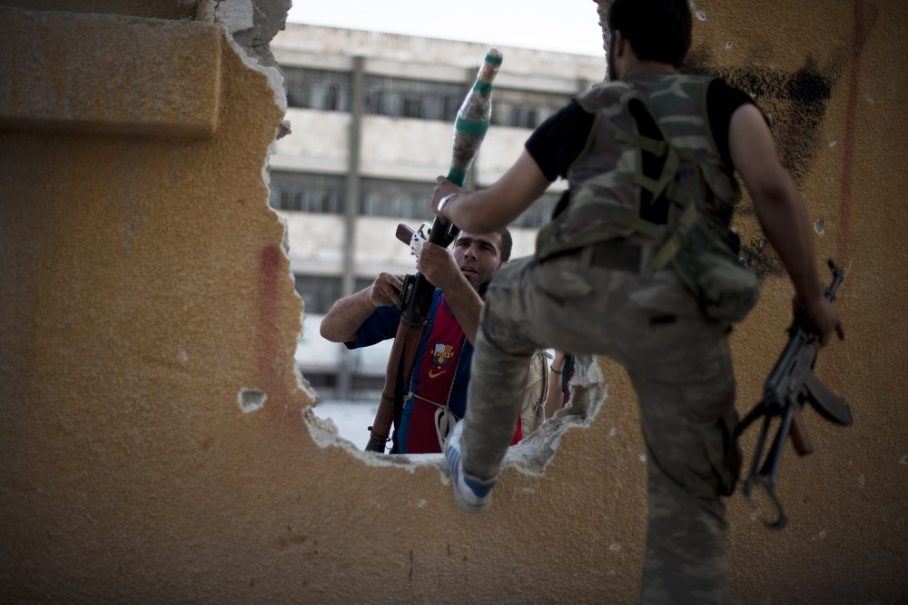 Fighters pass weapons through a hole in a building before an offensive against government forces in Izza neighbourhood of the embattled northern city of Aleppo AFP PHOTO / ZAC BAILLIE