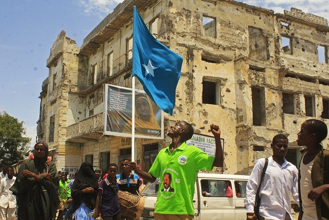 Man wearing a t-shirt with a picture of newly elected Somali President Hassan Sheikh Mohamud on it, waves a Somali flag as he celebrates in southern Mogadishu AFP PHOTO / ABDURASHID ABDULLE ABIKAR