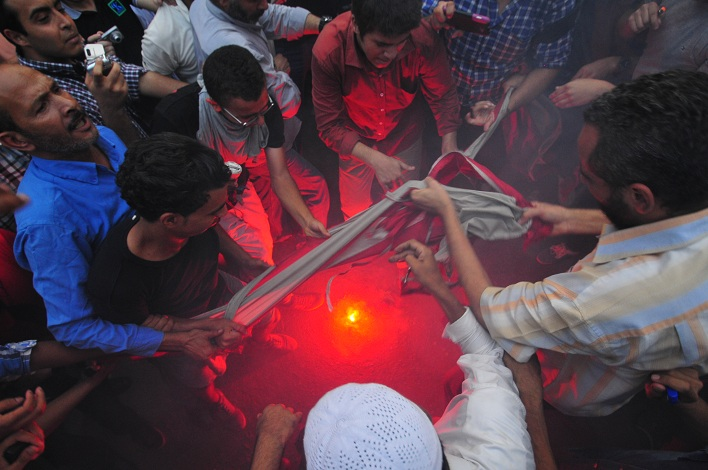 Demonstrators burn a United States flag taken from inside the American embassy grounds Hassan Ibrahim / DNE