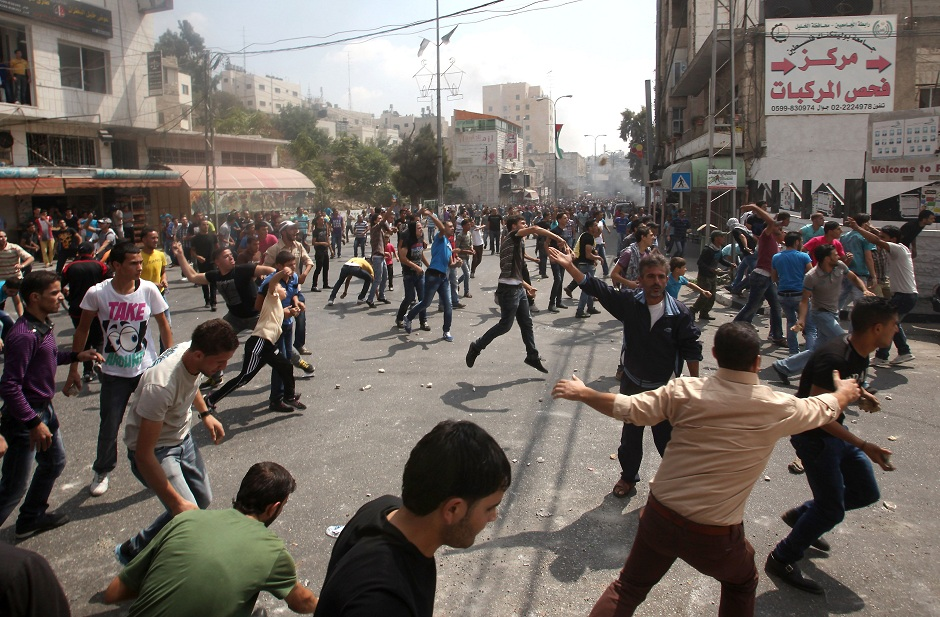 Palestinian protesters throw stones at police attempting to control the streets surrounding the municipality in the southern city of Hebron on 10 September after demonstrators hurled stones at the building AFP PHOTO / HAZEM BADER