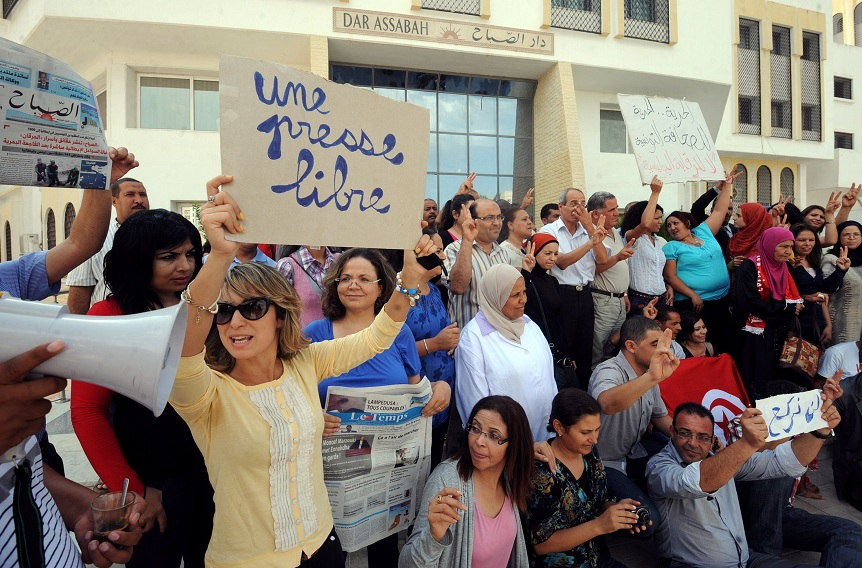 Tunisian journalists of Assabah daily hold signs calling for freedom of the press during a protest in Tunis on 11 September AFP PHOTO / KHALIL