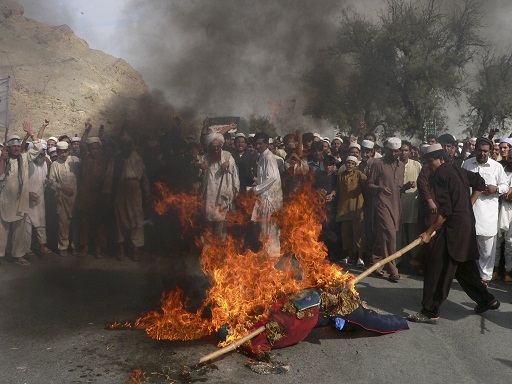Afghan demonstrators torch an effigy of US President Barack Obama during an anti-US demonstration in Ghanikhail district of Nangarhar province on 14 September AFP PHOTO / NOORULLAH SHIRZADA