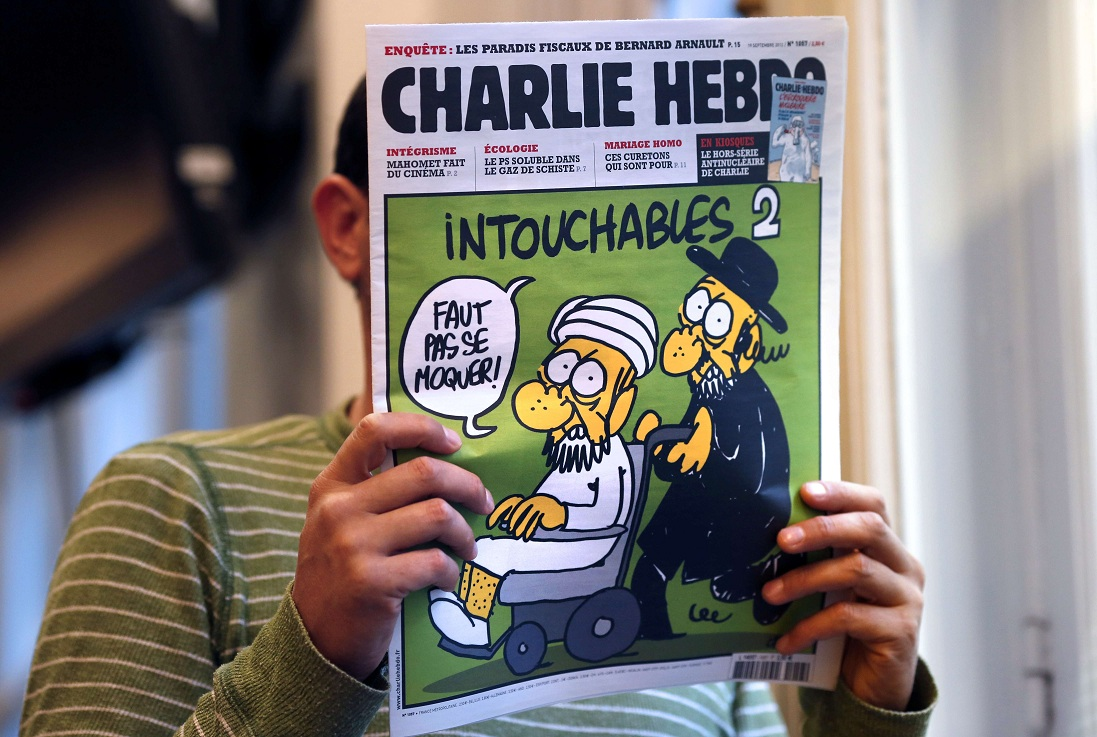 "A man reads the back cover of French satirical weekly Charlie Hebdo which features on the front covera satirical drawing titled ""Intouchables 2"". Inside pages contain several cartoons caricaturing the Prophet Mohammed AFP PHOTO / THOMAS COEX"