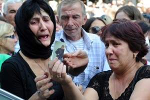 Women cry as they hold the picture of a relative during a protest rally against torture in prisons as demonstrators block one of the capital's main streets in Tbilisi AFP PHOTO / VANO SHLAMOV