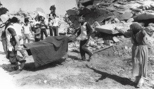 A picture dated 19 September 1982 shows a Palestinian woman crying while civil defence workers remove the body of one of her relatives from the rubble of her home in the Palestinian refugee camp of Sabra, in West Beirut AFP PHOTO