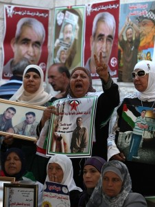 Palestinian women hold pictures of their relatives held in Israeli jails during a sit-in outside the Red Crescent offices near the West Bank city of Ramallah on 18 September (File photo) AFP PHOTO / ABBAS MOMANI