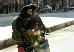 Syrian rebels armed with AK-47s ride a motorcycle in the northern city of Aleppo AFP PHOTO / MIGUEL MEDINA