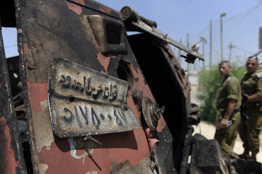 Israeli soldiers inspect a burnt armoured vehicle near the Karm Abu Salem border crossing after gunmen killed 16 Egyptian security officers and crossed into Israel on 6 August AFP PHOTO / DAVID BUIMOVITCH