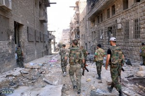 Syrian government forces walking along a street strewn with debris in the northern city of Aleppo during fighting against rebel forces AFP PHOTO / HO / SANA
