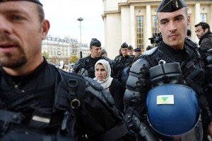 French mobile policemen escort a Muslim woman for an identity control in Paris as police deployed in several areas of the city to enforce a ban on protests over films and cartoons mocking the Prophet Mohammed AFP PHOTO / ERIC FEFERBERG