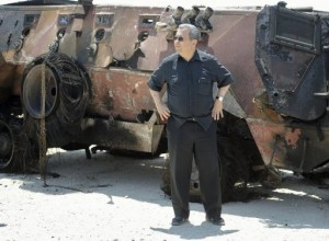 Israeli Defence Minister Ehud stand next to a burnt armoured vehicle near the Karam Salem border crossing on August 6, 2012