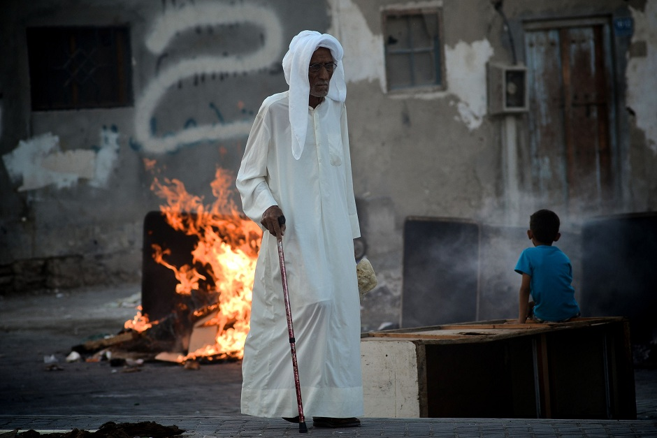 An elderly Bahraini man walks past a burning barricade set-up by protesters during clashes with the police following a demonstration in solidarity with jailed Bahraini opposition activists in Malekia, on the outskirts of the capital Manama on 4 September AFP PHOTO / MOHAMMED AL-SHAIKH