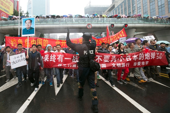 Chinese policeman directs protesters as they march and display anti-Japanese banners during a protest over the Diaoyu islands issue in Chengdu, southwest China's Sichuan province AFP PHOTO