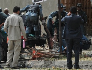 Afghan policemen carry the remains of a suicide attack victim in the city's diplomatic quarters in Kabul AFP PHOTO/ SHAH MARAI