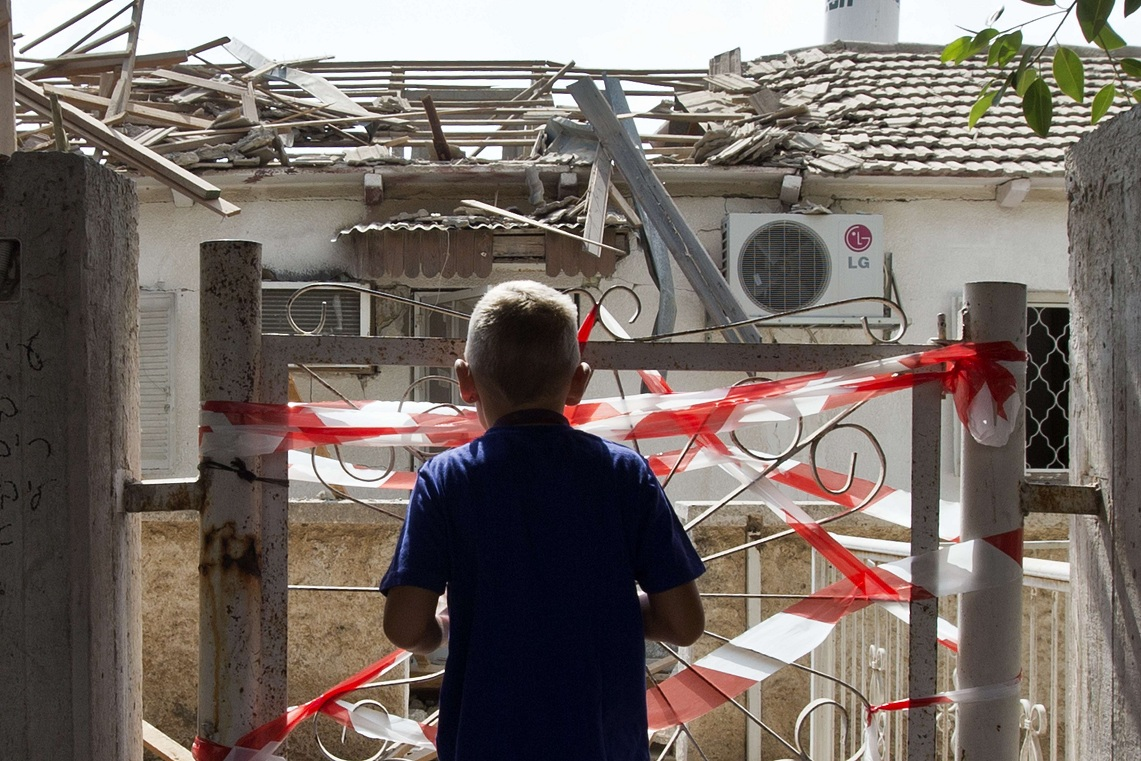 Israeli youth looks at the damages after a rocket fired by Palestinian militants from the Gaza Strip hit a house in the southern Israeli town of Netivot AFP PHOTO / JACK GUEZ