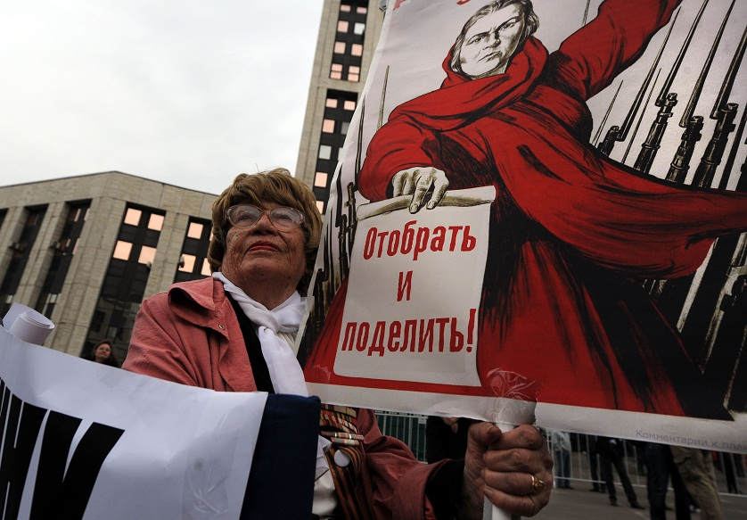 "Woman takes part in an anti-Putin protest in central in Moscow, the poster reads ""To take away and divide"" AFP PHOTO / ANDREY SMIRNOV"