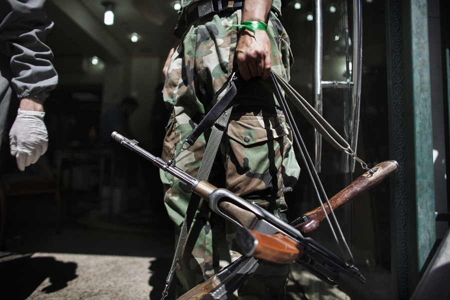 A Syrian rebel holds AK-47 rifles belonging to wounded comrades at the entrance to a hospital in the Sheikh Fares district of the northern city of Aleppo AFP PHOTO / MARCO LONGARI