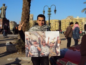 Protester on Tahrir Square carries an image of the 8 April officers 8 April group