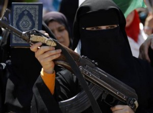 A Syrian woman holds an AK-47 during an anti-Bashar Assad protest after Friday prayers on the outskirts of Idlib, Syria AFP PHOTO
