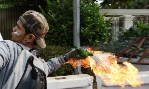 An Indonesian protester hurls a molotov coctail towards the US embassy in Jakarta AFP / Adek Berry