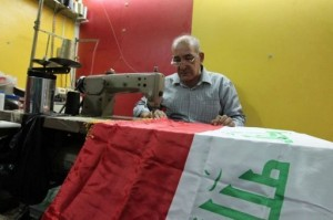 An Iraqi tailor sews a national flag at his workshop in Baghdad AFP Photo / Sabah Arar
