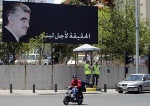 A Lebanese man rides his motorbike past a poster of slain premier Rafik Hariri in Beirut AFP/File, Joseph Eid