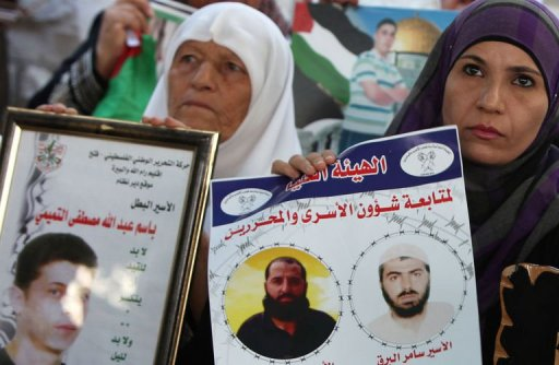 Palestinian women hold pictures of prisoners held in Israeli jails during a protest in Ramallah AFP / Abbas Momani