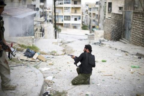 A fighter with the Free Syria Army fires his weapon during a skirmish with regime forces in the Izza districtb of Aleppo on Tuesday. Syrian troops and rebels clashed near Aleppo's international airport on Wednesday, a watchdog said, but it was unclear whether it was part of a rebel offensive to seize the facility AFP Photo