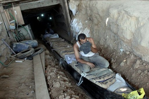 Palestinians transport bags of cement through smuggling tunnels under the Gaza-Egypt border in Rafah AFP, Mohammed Abed