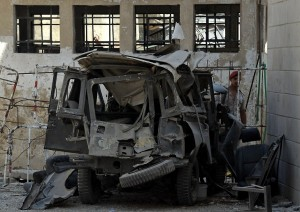 A handout picture released by the Syrian Arab News Agency (SANA) shows a member of the Syrian security forces inspecting the wreckage of a vehicle in Al-Mehdi Street in the Abu Remmaneh district of the Syrian capital Damascus on September 2, 2012 as Syrian state TV reported twin bombings near security service buildings in the centre of the capital and said they wounded four people. AFP PHOTO/HO/SANA