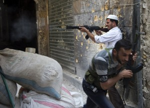 A Syrian rebel fires towards regime forces as his comrade ducks for cover during clashes in the old city of Aleppo in northern Syria AFP PHOTO / MIGUEL MEDINA