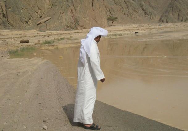 Man watches the flood waters near Nuweiba Nasser El-Azazy