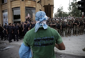 A supporter of the March 14 movement, which opposes the Syrian regime of President Bashar al-Assad, stands facing Lebanese security forces during a demonstration outside the governmental palace in Beirut after the funeral of top intelligence chief General Wissam al-Hassan and his bodyguard, in downtown Beirut, on October 21, 2012. Lebanese police fired in the air and used tear gas to repel protesters trying to storm the office of Lebanese Prime Minister Najib Mikati, amid calls for him to quit. (AFP Photo / Florian Choblet)