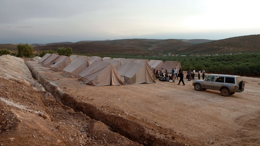Syrian volunteers set up tents for refugees in the northwestern Syrian village of Qah AFP PHOTO / HERVE BAR