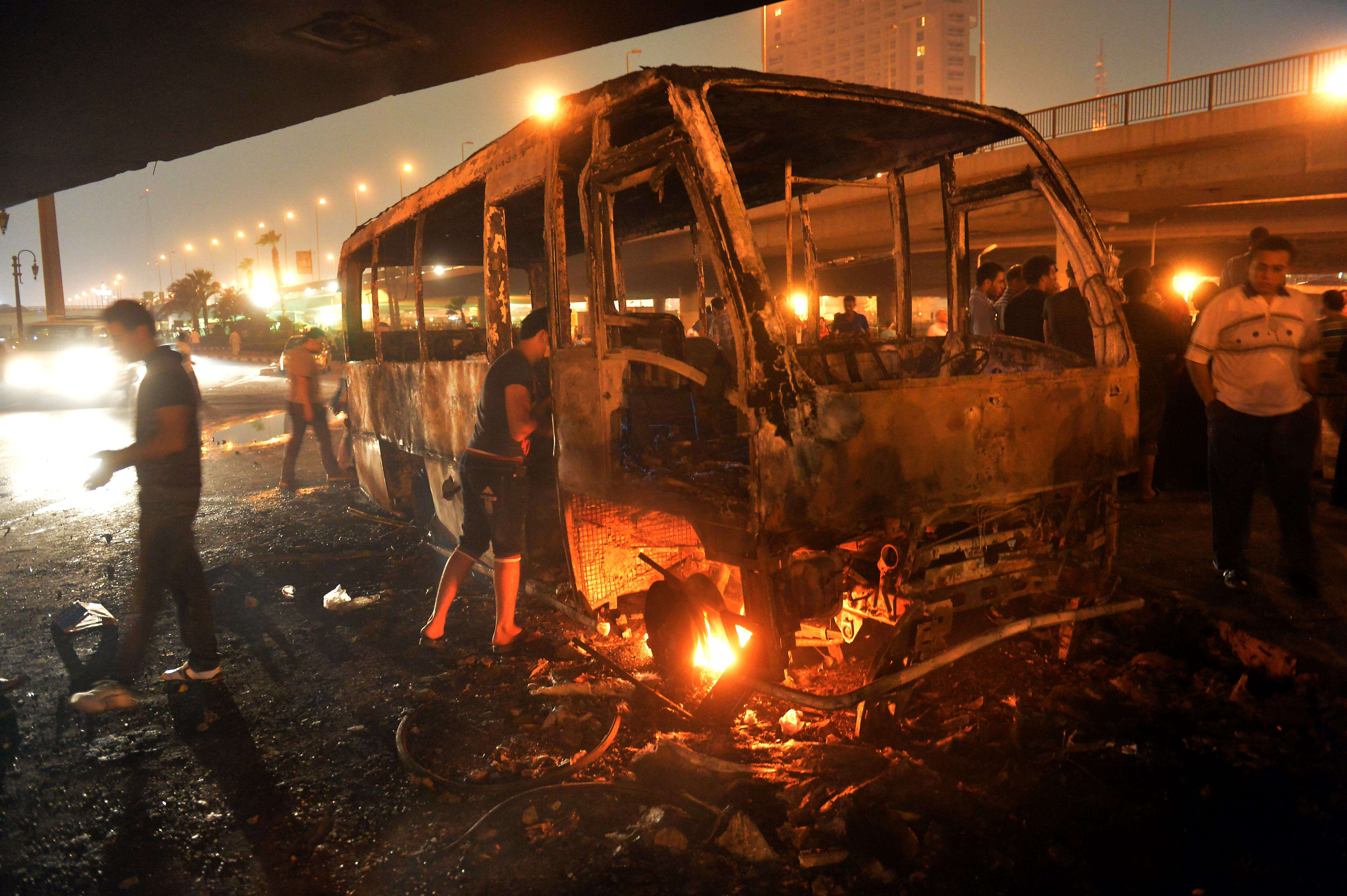 Egyptians inspect a burnt bus which was set on fire during clashes between government supporters and opponents of the Muslim Brotherhood and President Mohamed Morsi in Tahrir square in Cairo. (AFP/ KHALED DESOUKI)