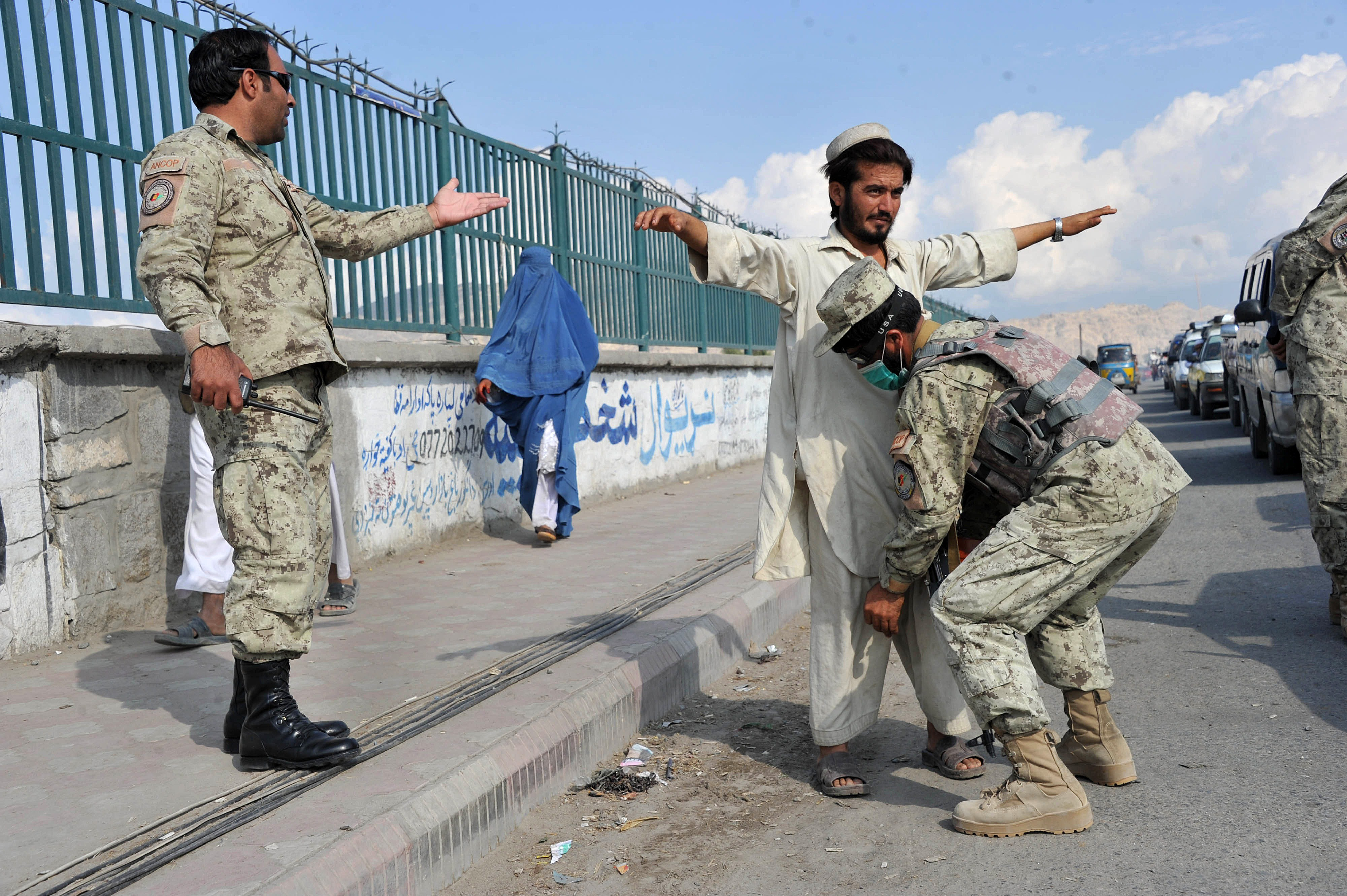 Afghan security personel check passengers and cars at a checkpoint in the city of Jalalabad in Nangarhar province on October 20, 2012. (AFP Photo/ Noorullah Shirzada)