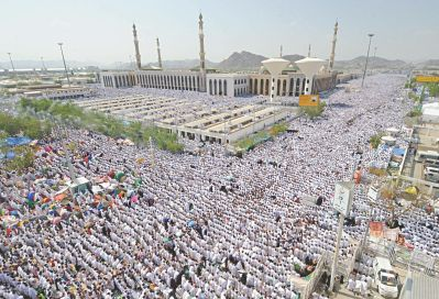 Pilgrims perform noon prayers outside the Namera Mosque (background) on the plain of Arafat on the outskirts of the holy city of Mecca. (AFP PHOTO)