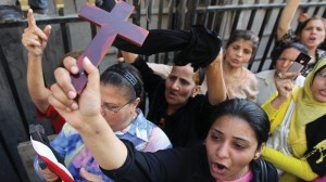 An Egyptian Coptic Christian raises a cross while others shout slogans during a demonstration outside the Cairo High Court. ( AFP File Photo/ Khaled Desouki)