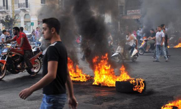 Protesters gather on motorbikes at a road block of burning tires in the northern Lebanese city for Tripoli as they demonstrate against the murder of General Wissam Al-Hassan. (AFP Photo)