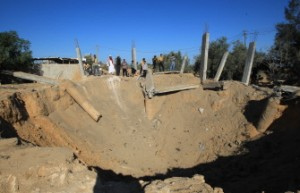 Palestinians inspects a crater following an Israeli attack in Al-Bureij center of the Gaza Strip on October 29, 2012. (AFP PHOTO / MAHMUD HAMS)
