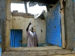 A man points to damage at his house caused by rebel fire. (AFP/ Ashraf Shazly)