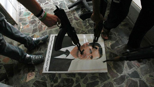 Free Syrian Army soldiers point guns at a portrait of President Bashar Al-Assad. (AFP PHOTO / ADEM ALTAN)