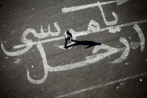 "A man walks over a graffiti reading ""Morsy Go"" on Tahrir square in Cairo. (AFP PHOTO / MAHMOUD KHALED)"