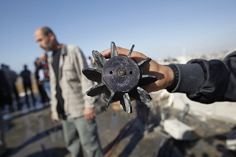 A Palestinian youth shows the remains of an Israeli missile following an air strikes in the Jabalia refugee camp. (AFP PHOTO / MOHAMMED ABED)