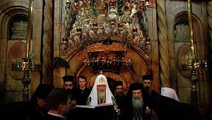 Greek Orthodox Patriarch of Jerusalem Theophilos III (right) and Russian Orthodox Patriarch Kirill (centre) pray in front of Christ's tomb at the Church of the Holy Sepulchre. (AFP / FILE PHOTO / GALI TIBBON)