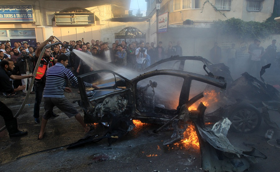 Palestinians extinguish fire from the car of Ahmaed Jaabari, head of the military wing of the Hamas movement, the Ezzedin Qassam Brigades, after it was hit by an Israeli air strike in Gaza City (Photo by AFP / Mahmud Hams)