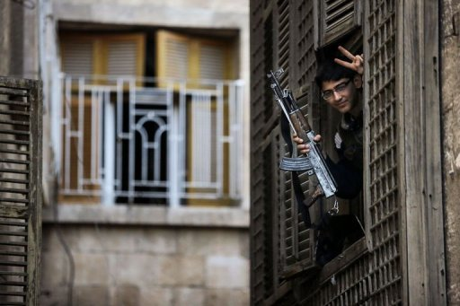 A Syrian student-turned-rebel makes a victory sign from his post in an ancient building in Aleppo (Photo by AFP / John Cantlie)