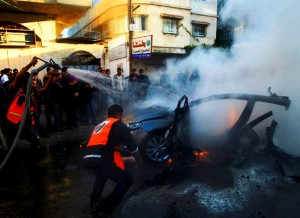 Palestinians extinguish fire from the car of Ahmaed Jaabari, head of the military wing of the Hamas movement, the Ezzedin Qassam Brigades, after it was hit by an Israeli air strike in Gaza City on November 14, 2012. (AFP PHOTO / MAHMUD HAMS)(